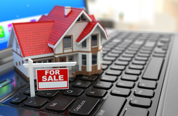 House Model placed on the laptop - Real Estate Digital Marketing